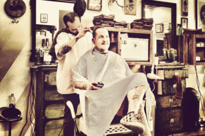 En barber arbejder med klassisk herreklipning og knivbarbering